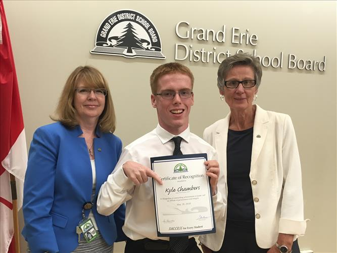 A young man smiles while holding a certificate with two staff members posing with him