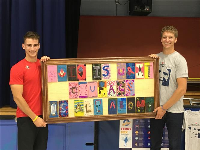 A teacher and an athlete hold up a poster with inspiring message