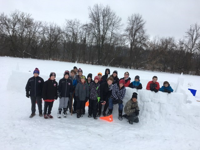 A group of students wearing snowsuits stands in front of a snow fort