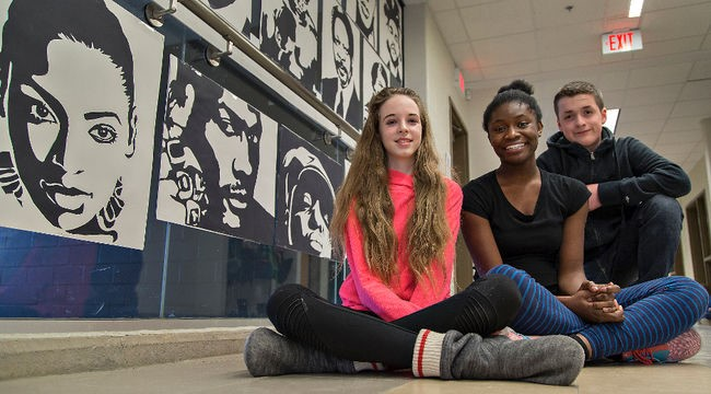 Students sit in a hallway in front of artistic works of sillouettes of figures from Black History
