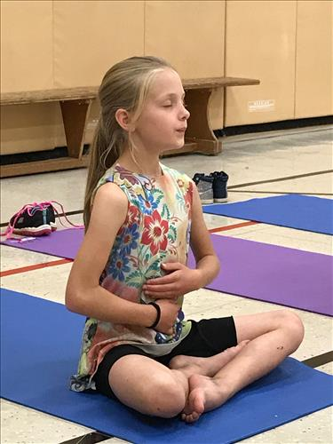 A young student sits on a yoga mat
