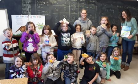 A group of young students smiles while holding healthy snacks