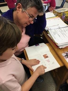 A volunteer assists a student reading a book