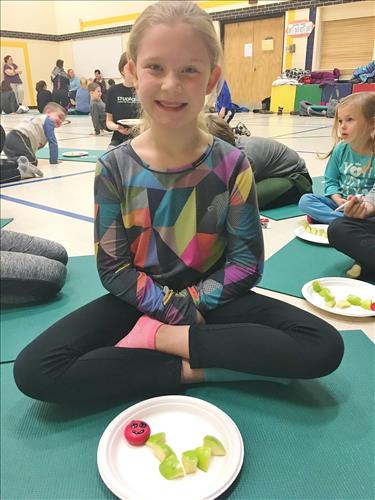 A young girl sits cross-legged on a yoga mat in a school gym