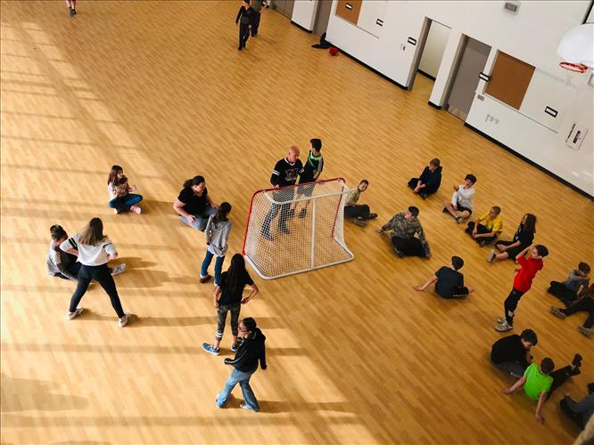 Students play a game in a gym