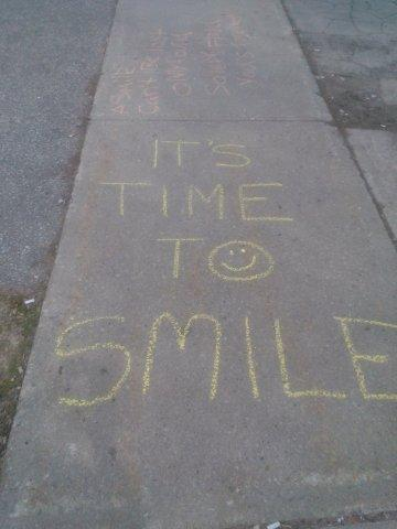 A chalk drawing says It's Time to Smile