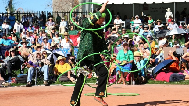 A male in regalia performs a hoop dance