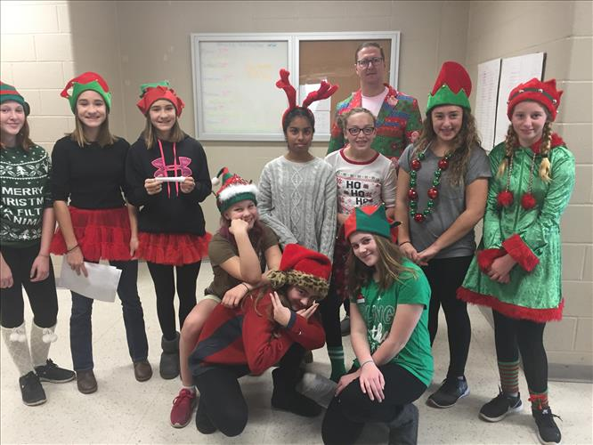 A group of students wearing holiday elf hats organizes canned goods