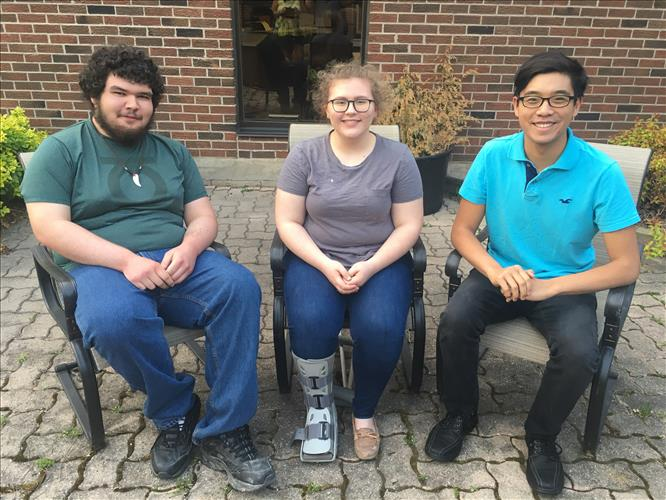 Two male and one female student are seated, smiling