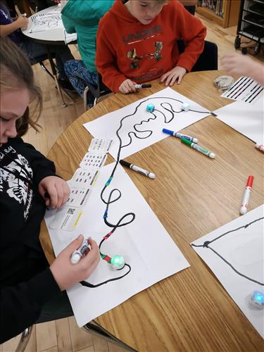 Students work with tech devices on a table top