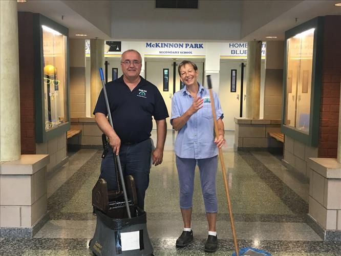 Two custodians in uniform pose in a school hallway