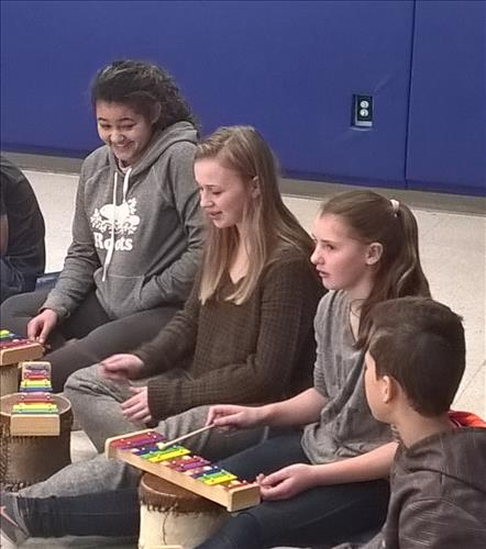 Students develop rhythm using traditional drums