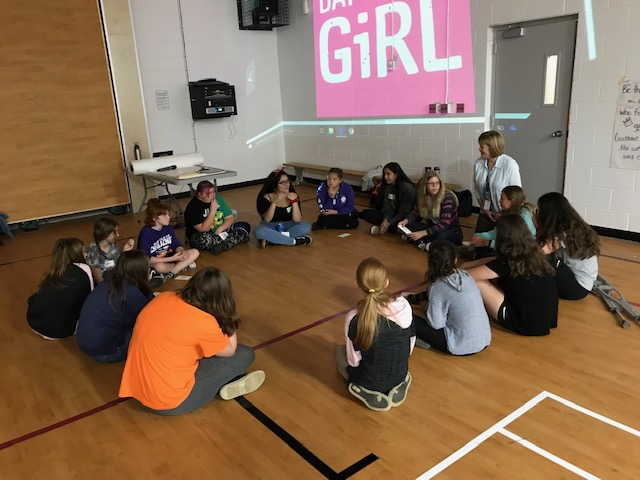 A small group of female students sits in a circle