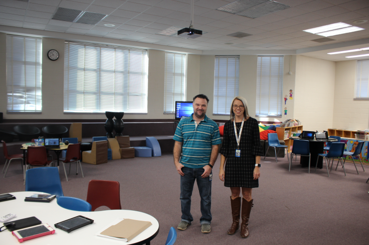 Two teachers stand among the Learning Commons space