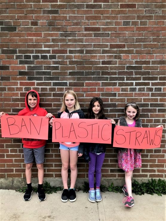 Students hold signs calling for ban on plastics