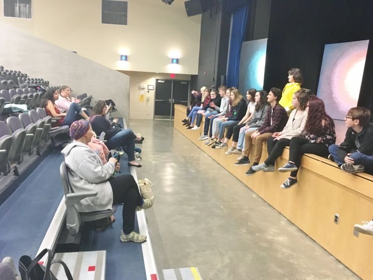 A group of students sits on stage following play rehearsal