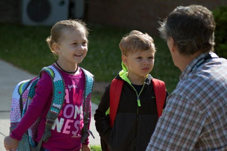 A teacher kneels down to speak to two children