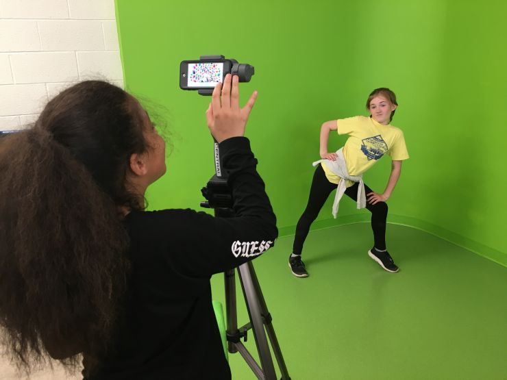 Two students use a green screen