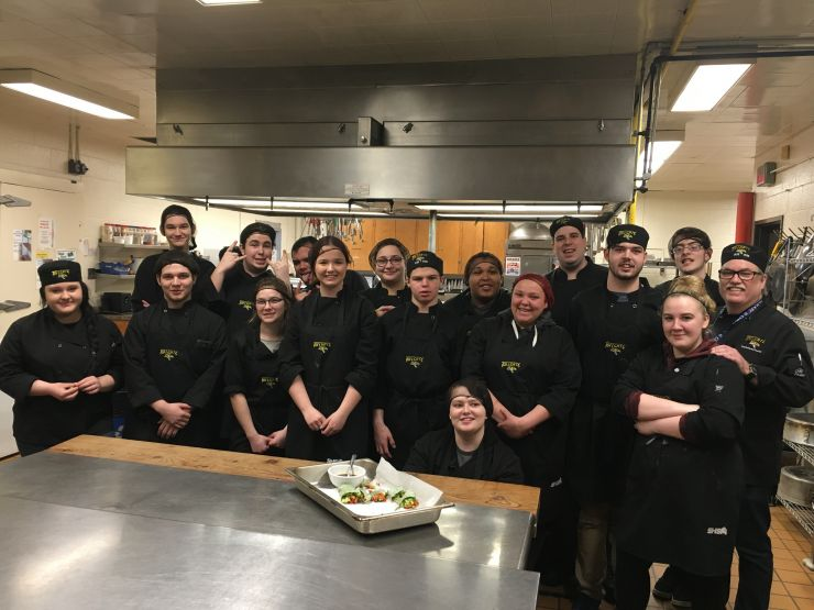 A large group of people poses in a kitchen