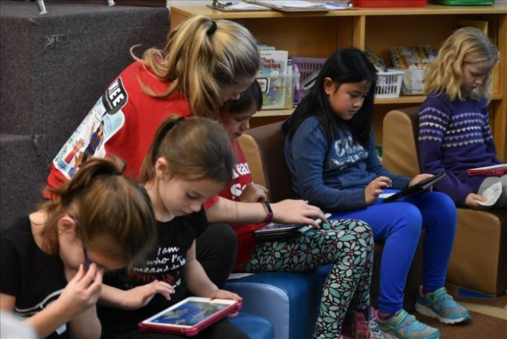 Students participate in a coding exercise on tablet devices in a learning commons