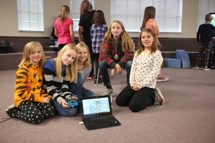 A small group of girls poses with a laptop and robot