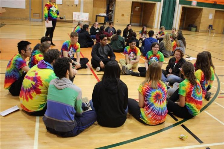 A group of students works on a team-building activity in a gym