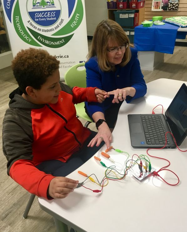 A woman is instructed by a young student using Makey-Makey technology