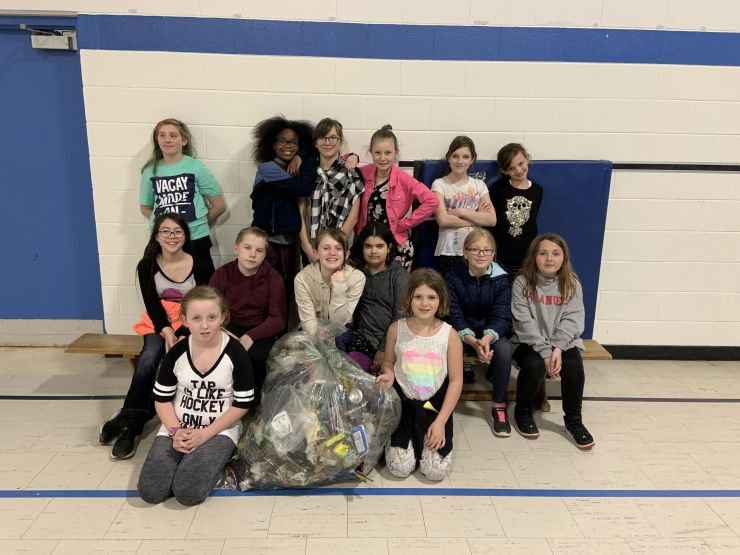 Students pose with a large bag of garbage they collected