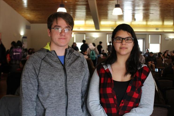 Two students pose with a crowd behind them
