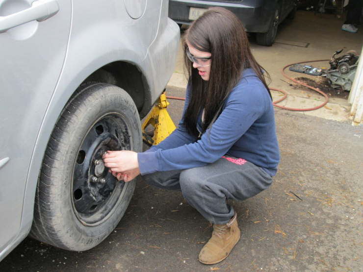 A female student works on the wheel hub of a car