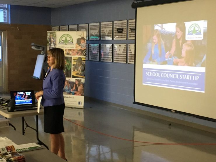 Director of Education Brenda Blancher stands in front of a projected image during a presentation