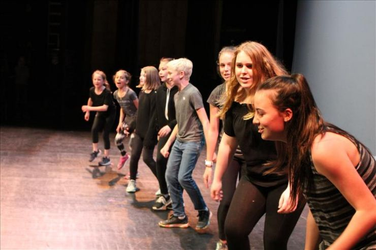 A group of students performs a scene on stage