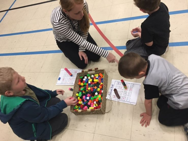 Students and parents use math manipulatives during a workshop