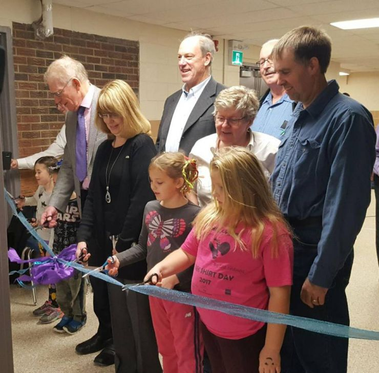 A group of students and staff cuts a ribbon in a school hallway