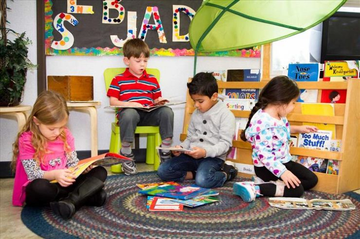A group of four Kindergarten students sits on a mat playing with toys and books