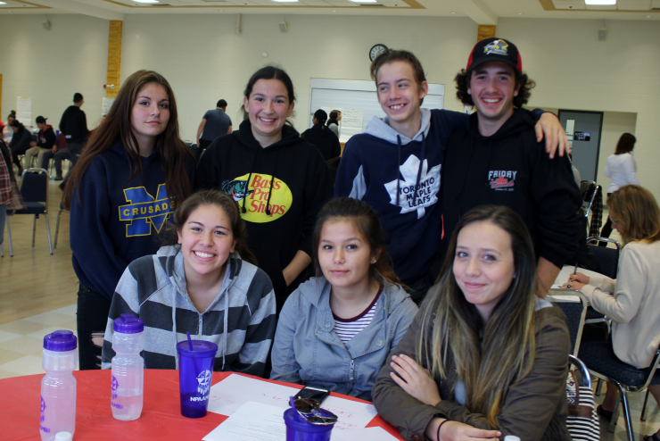 Seven student leaders pose at a table during an event