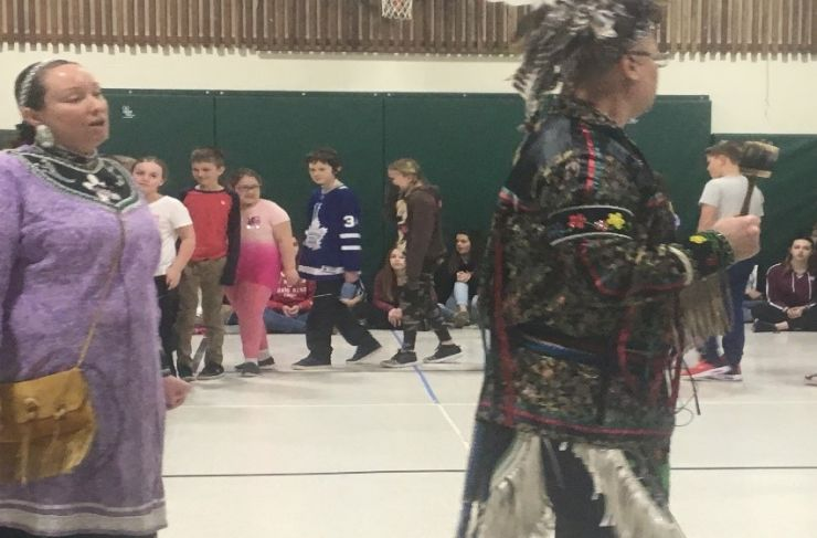 Indigenous dancers lead a group of students