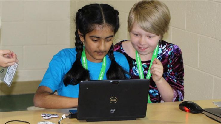 Two young students code on a computer