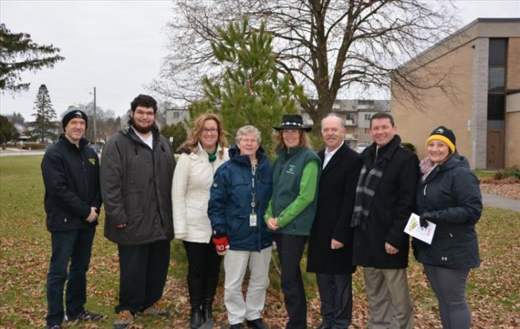A group of students and staff stands in front of a newly planted tree