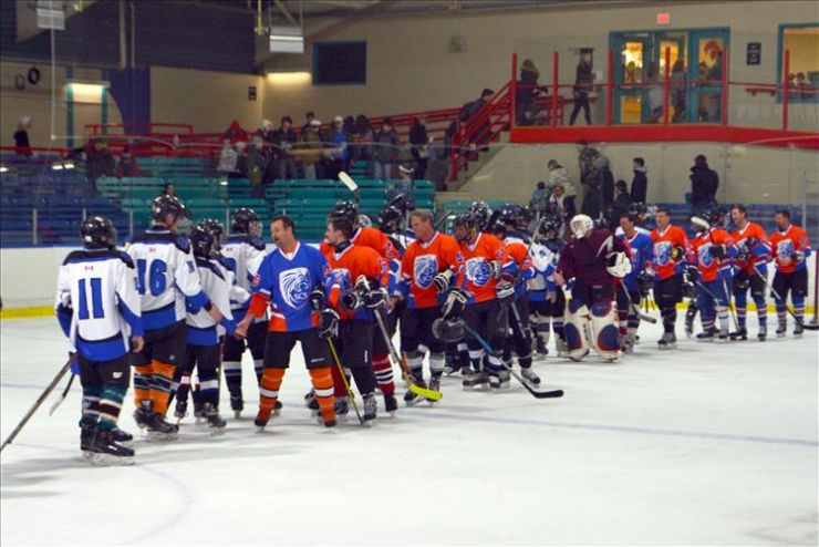 Two hockey teams shake hands on the ice