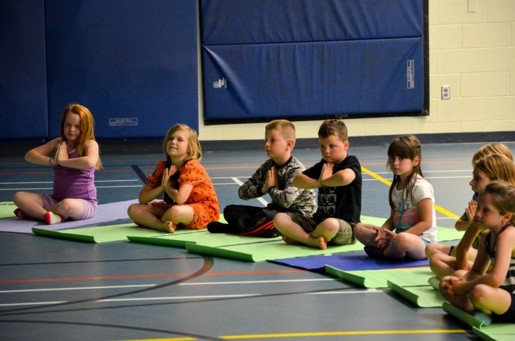 A group of children sit cross-legged on yoga mats with hands folded