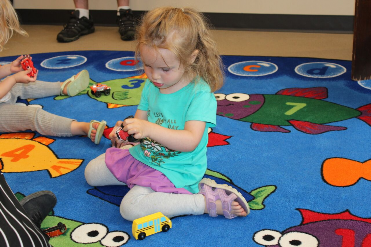 A child plays with toys on a colourful mat
