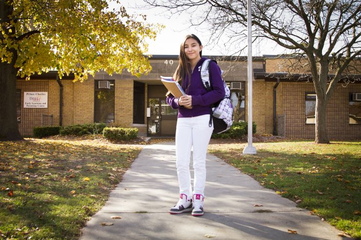 A female student stands in front of a school with books in her arms