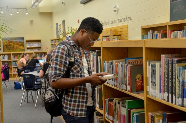 An older male student reads a book while standing in front of a bookshelf in a library