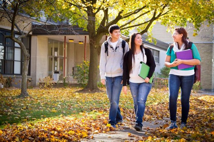 Three students walk through an autumn landscape