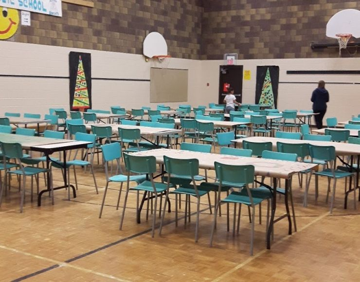 A school gym is transformed into a food hall with rows of tables and chairs