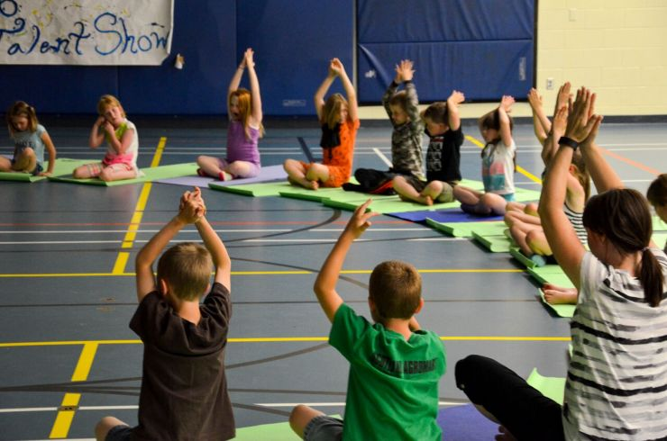 A group of students sit on yoga mats with their arms in the air