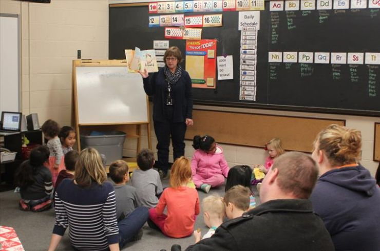 A Child and Youth Worker reads a story to a group of Grade 1 students