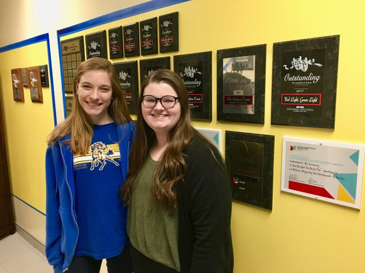 Two female students pose in front of a wall of theatre awards