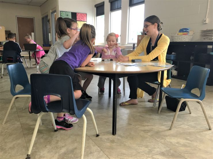 A teacher sits at a table with Kindergarten students